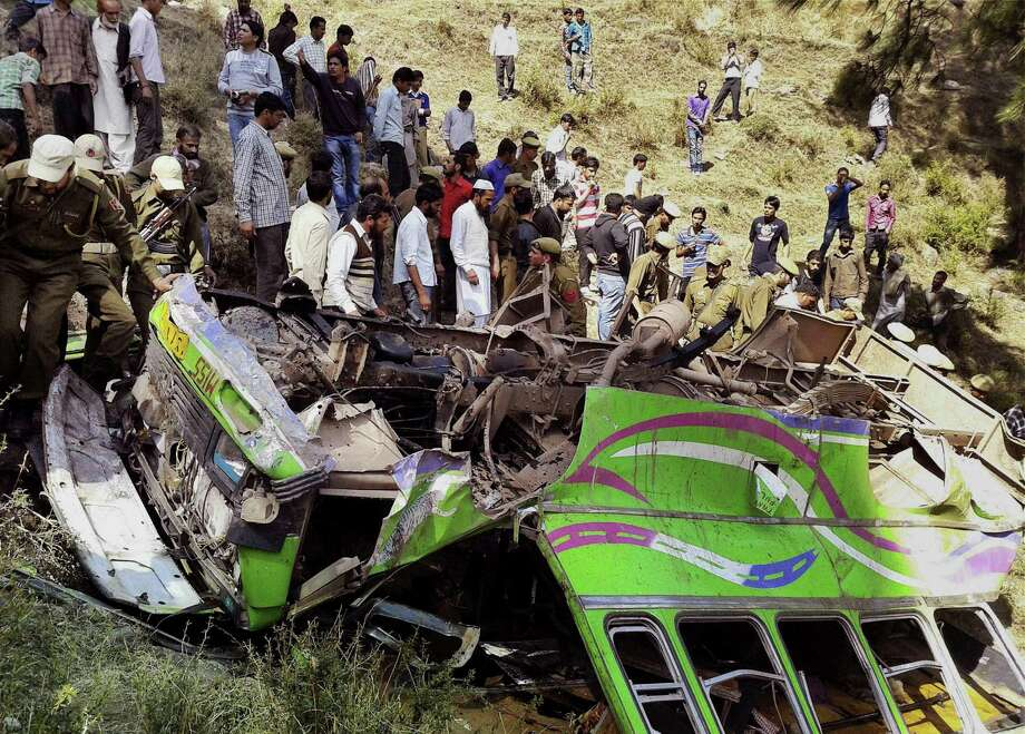 Indian people and policemen, in uniform, gather after a bus accident at Rajouri district in Jammu, India, Friday. Fifteen people were killed and 24 injured when a bus rolled down into a deep gorge, according to local reports. Photo: AP