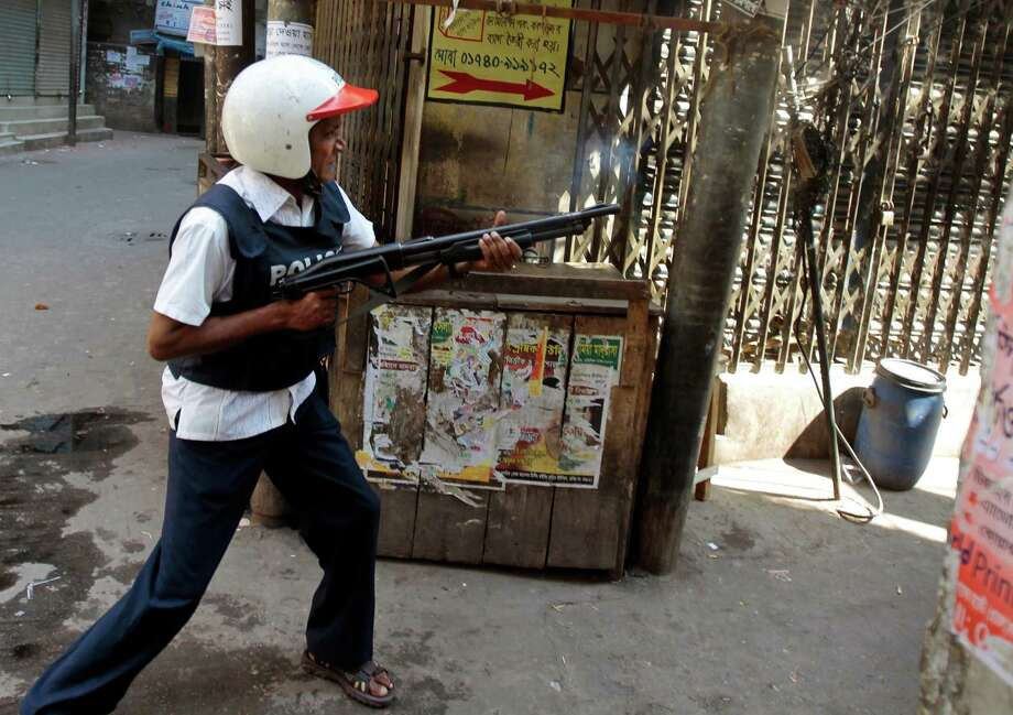 A Bangladeshi police officer fires rubber bullets after largest Islamic party Jamaat-e-Islami activists clashed with them in Dhaka, Bangladesh, Friday. The fight for the future of Bangladesh is playing out in the streets of this troubled south Asian nation. For a month, masses of moderate activists have camped at a Dhaka intersection demanding harsh punishment for those accused of crimes during the 1971 independence war from Pakistan, a stance that dovetails with the prime minister's position. Photo: AP