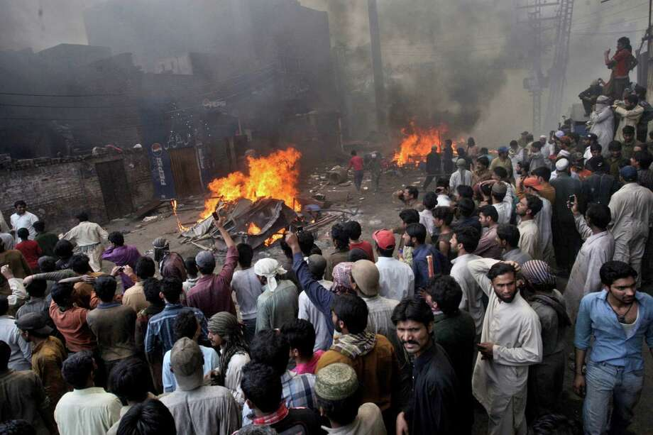 An angry mob gathers after burning Christian houses, in Lahore, Pakistan, Saturday. A mob of hundreds of people in the eastern Pakistani city of Lahore attacked a Christian neighborhood Saturday and set fire to homes after hearing accusations that a Christian man had committed blasphemy against Islam's prophet, said a police officer. Photo: AP