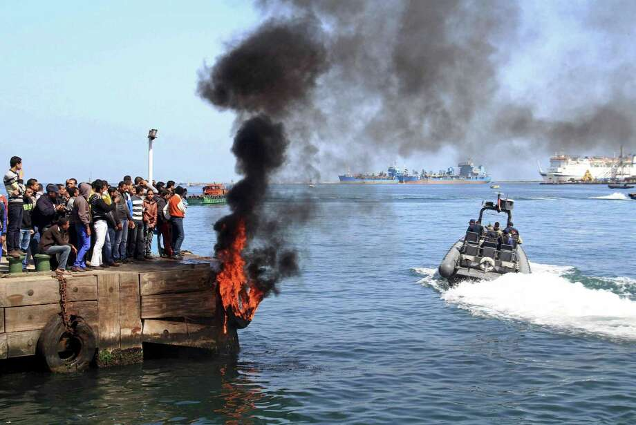 Several protesters set fire to tires on the city's dock in an attempt to prevent ships from coming in to the strategic city of Port Said at the Mediterranean end of the Suez Canal, in Egypt, Saturday. An Egyptian court on Saturday confirmed the death sentences against 21 people for taking part in a deadly 2012 soccer riot but acquitted seven police officials for their alleged role in a trial that has been the source of some of the worst unrest to hit Egypt in recent weeks. Photo: AP