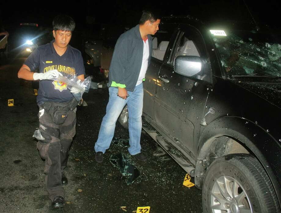 In this Jan. 6 photo released by the Philippine National Police Quezon Provincial Director's Office, Quezon provincial police chief Valeriano de Leon, right, looks at a bullet-riddled vehicle at a checkpoint along a road in the town of Atimonan in Quezon province, southeast of Manila, Philippines. Security personnel originally claimed the incident as a shootout with suspected criminals, but the Philippine justice secretary said Wednesday, March 7, investigators will file a murder case against 35 police officers and soldiers for allegedly executing 13 people at the road checkpoint in a plan by a police colonel to eliminate a rival in an illegal gambling operation. Photo: AP