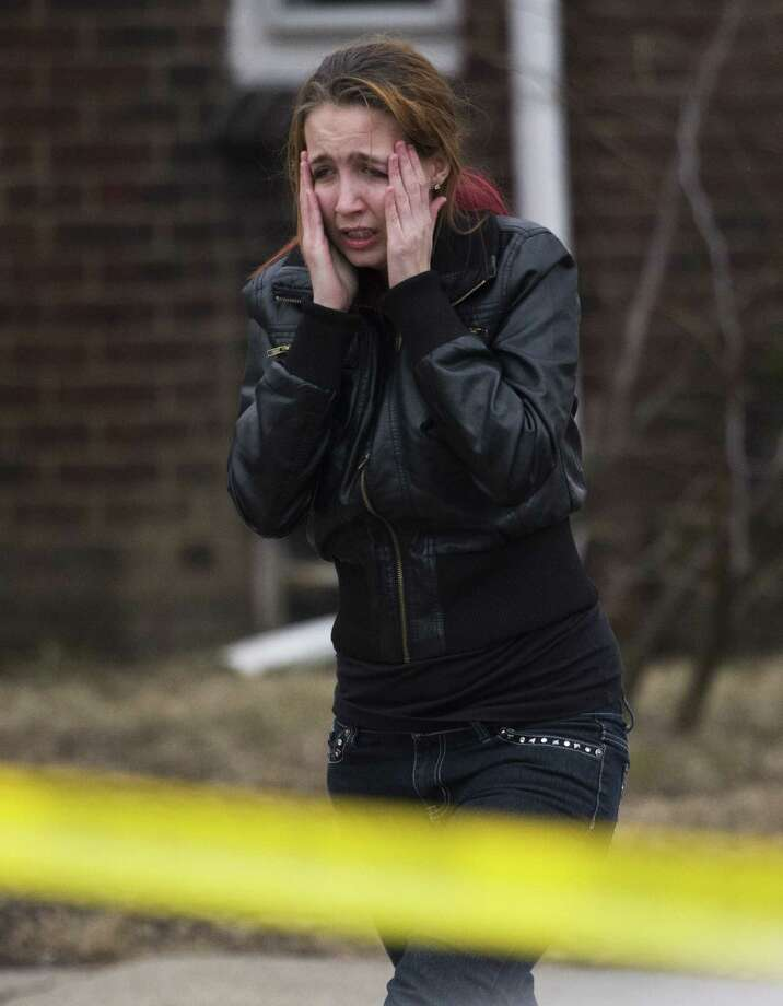 A mourner walks away from the scene where three bodies were found in a house at 11000 block of Coyle Street in Detroit on Thursday. A woman says a 5-year-old girl watched as a man fatally shot her mother and two other people to death at a house on Detroit's northwest side. Photo: AP