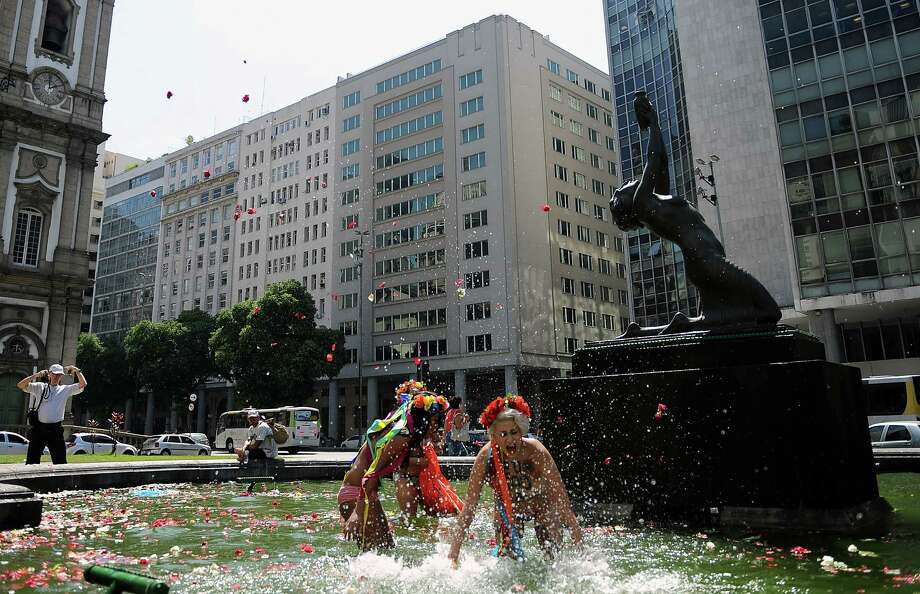 Topless activists of the women's rights group Femen Brazil stage a protest against homophobia at a fountain in front of the Candelaria church in Rio de Janeiro on Saturday. Photo: VANDERLEI ALMEIDA, Getty / 2013 AFP