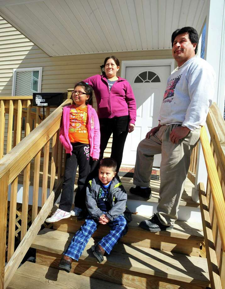 Maria and Manuel San Martin stand with their children, Katherine, 7, and Eric, 4, on the front deck of their new Danbury home, provided by Housatonic Habitat for Humanity, Sunday, March 10, 2013 in Conn. Photo: Michael Duffy / The News-Times