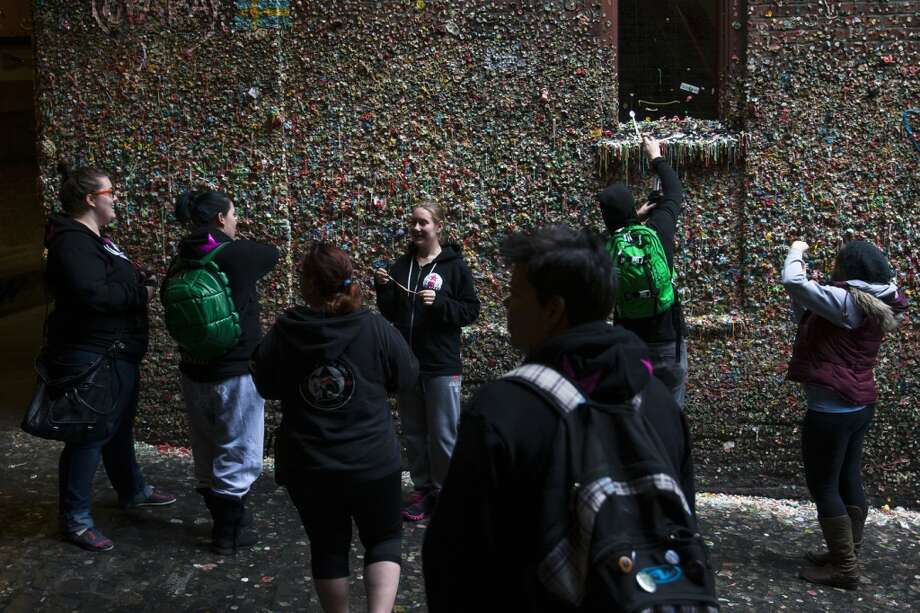Tourists snap pictures of Pike Place Market's famous Gum Wall on Thursday, Feb. 28, 2013, in Seattle. (Jordan Stead, seattlepi.com)