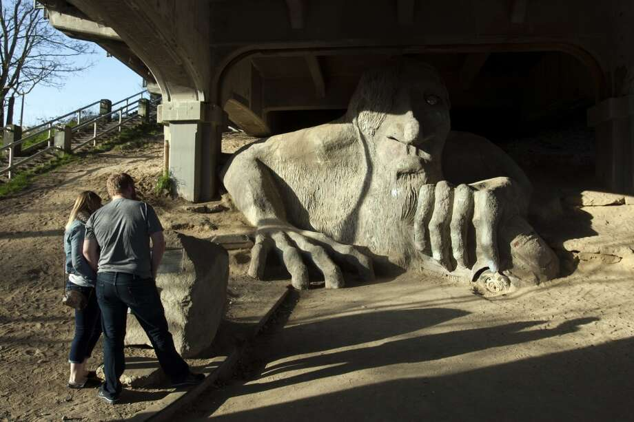 A couple enjoys the Fremont Troll (under the Aurora bridge) on Monday, March 4, 2013, in Seattle. (Jordan Stead, seattlepi.com)