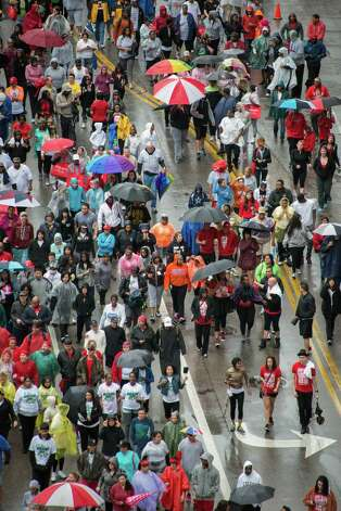 Participants walk along Bagby Street at the start of the 24th Annual AIDS Walk Houston on Sunday, March 10, 2013, in Houston. Proceeds participants raise from the event benefit AIDS Foundation Houston as well as several other HIV/AIDS service organizations. Photo: Smiley N. Pool, Houston Chronicle / © 2013  Houston Chronicle