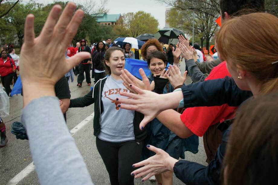 Volunteers at a water stop exchanged high-fives with walkers along Allen Parkway. Photo: Smiley N. Pool, Houston Chronicle / © 2013  Houston Chronicle