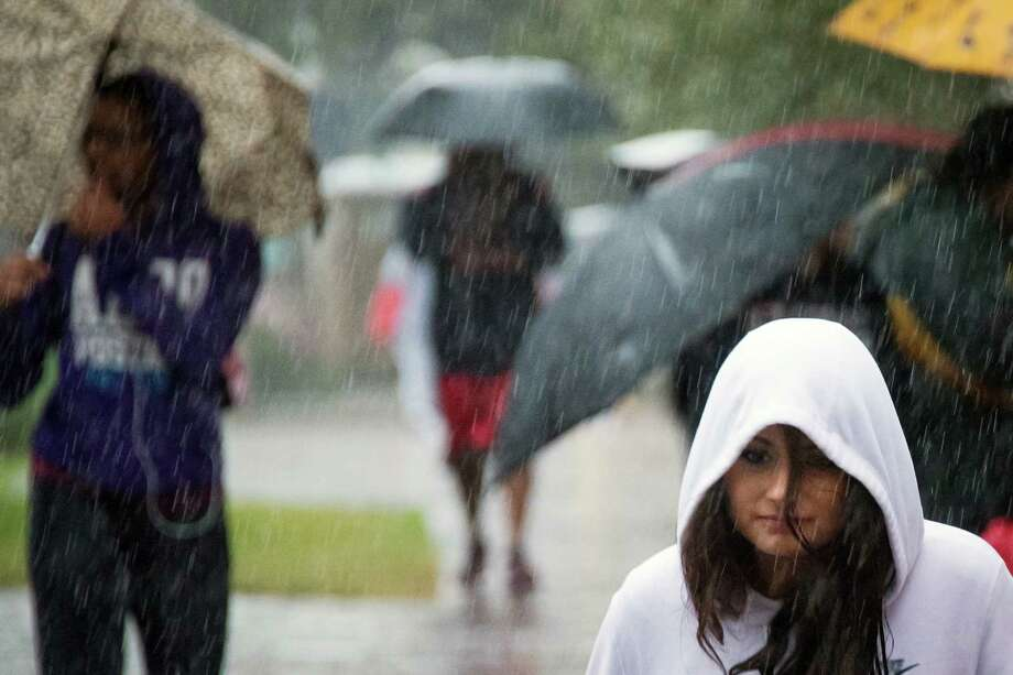 Participants try to find cover from the rain before the walk. Photo: Smiley N. Pool, Houston Chronicle / © 2013  Houston Chronicle