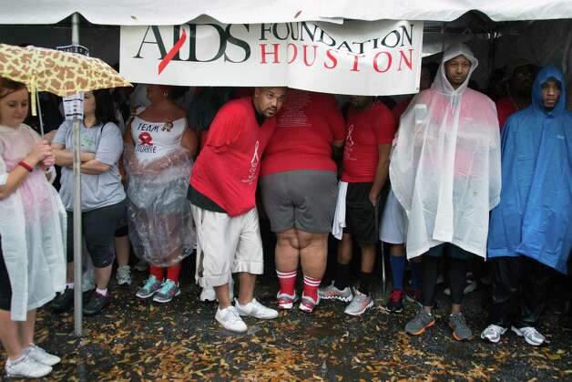 The AIDS Foundation Houston tent provides cover from the rain as walkers wait for the start of the walk. Photo: Smiley N. Pool, Houston Chronicle / © 2013  Houston Chronicle