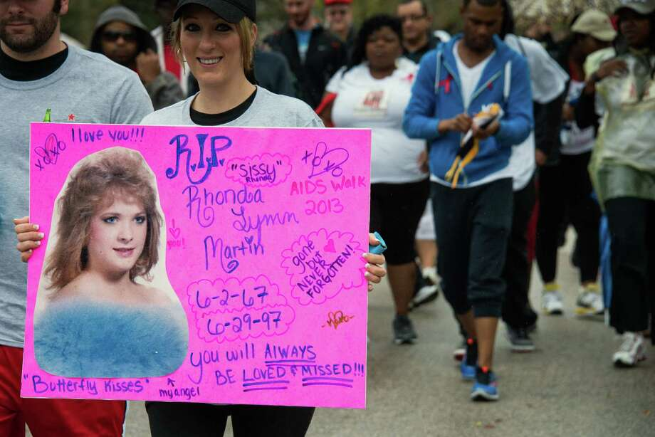 "Krista Thrasher holds a poster honoring her sister Rhonda Martin during the walk. Martin died from AIDS in 1997, and Thrasher has participated in the walk every year since to honor her memory.  ""She was such a trooper, she was always positive,"" Thrasher said. Photo: Smiley N. Pool, Houston Chronicle / © 2013  Houston Chronicle"