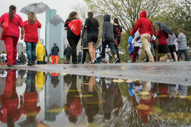 Puddles from the morning's rain frame walkers along Allen Parkway. Photo: Smiley N. Pool, Houston Chronicle / © 2013  Houston Chronicle