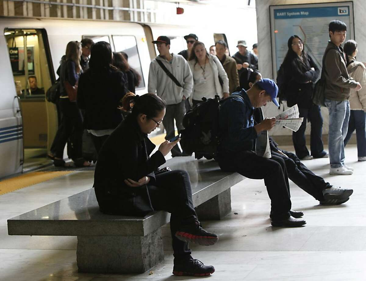 A BART rider checks her phone before getting on BART at the Balboa Park Station in San Francisco, Calif., Tuesday May 15th, 2012.