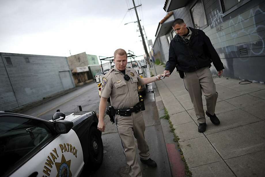 California Highway Patrol Officer Robert Koehn (right) hands Officer Sean Deise paperwork during a traffic stop in East Oakland. The city has approved additional funding for California Highway Patrol officers. Photo: Michael Short, Special To The Chronicle