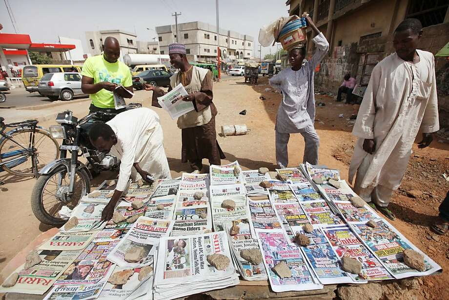 People read local newspapers with headlines like ' We've killed 7 foreign hostages' on a street in Kano, Nigeria, Sunday, March. 10, 2013. The United Kingdom's military says its warplanes recently spotted in Nigeria's capital city were there to move soldiers to aid the French intervention in Mali,not to rescue kidnapped foreign hostages. The Ministry of Defense said Sunday that the planes had ferried Nigerian troops and equipment to Bamako, Mali. An Islamic extremist group in Nigeria called Ansaru partially blamed the presence of those planes as an excuse for claiming Saturday that it killed seven foreign hostages it had taken. ( AP Photo/Sunday Alamba) Photo: Sunday Alamba, Associated Press