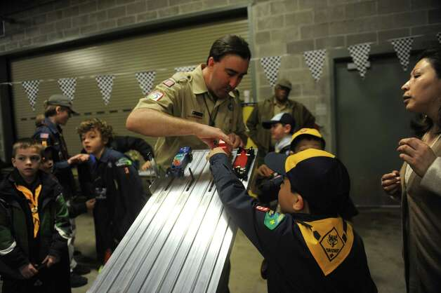 Kevin O'Shea, scout executive/CEO of the Greenwich Council, places the boy's cars to start the race at the Greenwich Cub Scouts race in pinewood derby at Greenwich Police Department in Greenwich, Conn., Sunday March 10, 2013. Photo: Helen Neafsey / Greenwich Time