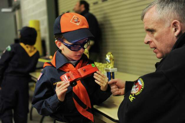 Scout Robert Parry, 7, shows his car to Greenwich Police Chief James Heavey at the Greenwich Cub Scouts race in pinewood derby at Greenwich Police Department in Greenwich, Conn., Sunday March 10, 2013. Photo: Helen Neafsey / Greenwich Time