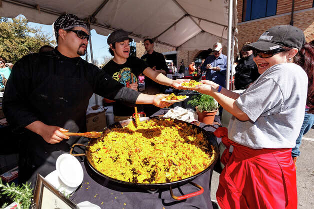Elia Jasso receives a plate of paella from J.C. Rodriguez (center) and Chef Jeff Balfour during the 4th Annual Corona Paella Challenge, hosted by La Gloria chef, Johnny Hernandez, on the grounds of the Pearl Brewery on Sunday, March 10, 2013.  Twenty-five of the top chefs in this country and throughout Latin America competed in the event as well as five area high schools. Photo: Marvin Pfeiffer / San Antonio Express-News / Express-News 2013