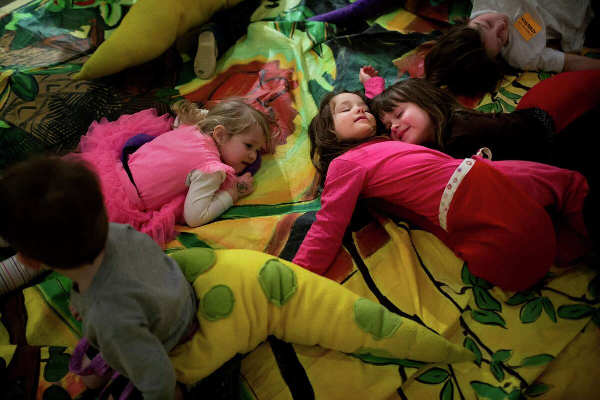 Wearing fluffy dinosaur tails amidst a sea of other children, Madeleine Manville, 5, in pink and red, snuggles with friend Nina Silverman, 5, in brown, during the annual Dino Day event Sunday, March 10, 2013, at the Burke Museum in Seattle.