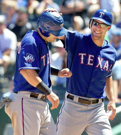 Texas Rangers' David Murphy, right, celebrates with teammate Mitch Moreland after the pair scored on a triple by Elvis Andrus during the fourth inning of a baseball game against the Kansas City Royals at Kauffman Stadium in Kansas City, Mo., Sunday, Aug. 5, 2012. (AP Photo/Orlin Wagner) Photo: Orlin Wagner, Associated Press / AP