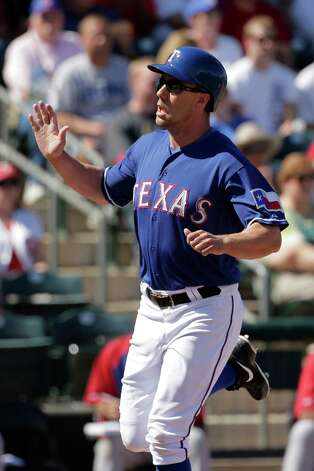 Texas Rangers' David Murphy runs home to score during an exhibition spring training baseball game against the Chicago Cubs Wednesday, March 6, 2013, in Surprise, Ariz. (AP Photo/Charlie Riedel) Photo: Charlie Riedel, Associated Press / AP