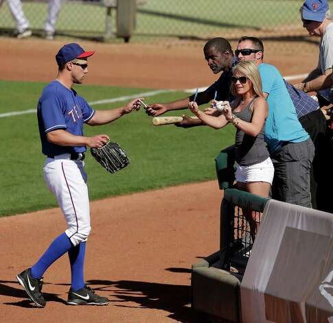 Texas Rangers' David Murphy signs autographs as he leaves the field during the seventh inning of an exhibition spring training baseball game against the Chicago Cubs Wednesday, March 6, 2013, in Surprise, Ariz. (AP Photo/Charlie Riedel) Photo: Charlie Riedel, Associated Press / AP