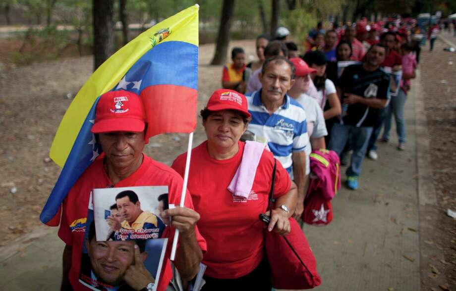 People queue outside the military academy where Venezuela's late President Hugo Chavez is lying in state in Caracas, Venezuela, Sunday, March 10, 2013. Chavez died on March 5 after a nearly two-year bout with cancer. He was 58. (AP Photo/Ariana Cubillos) Photo: Ariana Cubillos