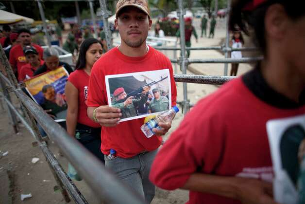 People enter the military academy to see the body of Venezuela's late President Hugo Chavez lying in state in Caracas, Venezuela, Sunday, March 10, 2013. Chavez died on March 5 after a nearly two-year bout with cancer. He was 58. (AP Photo/Ariana Cubillos) Photo: Ariana Cubillos