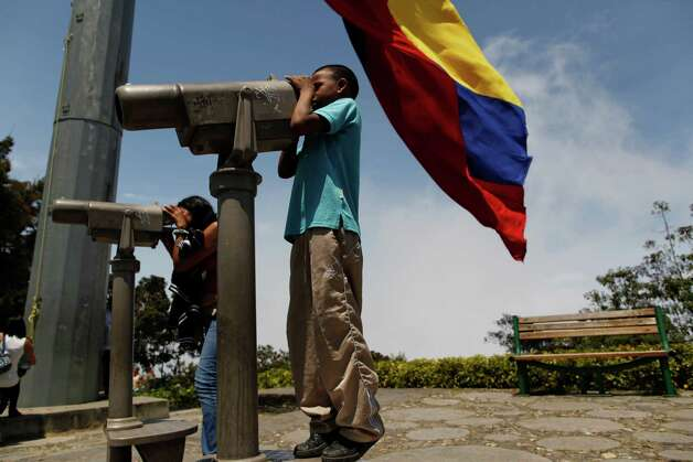 Under a Venezuelan flag, a boy, right, stands on tiptoes to watch the city through a paid telescope from the Avila, the mount overlooking the city of Caracas, Venezuela, Sunday, March 10, 2013. Venezuela's President Hugo Chavez died of cancer on March 5. Venezuela's electoral council set April 14 as the date for the country's presidential election to choose a successor. (AP Photo/Rodrigo Abd) Photo: Rodrigo Abd