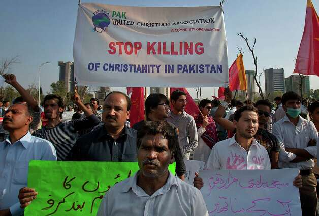 Pakistani Christians hold posters during a demonstration demanding that the government rebuild their homes after they were burned down following an alleged blasphemy incident in Islamabad, Pakistan, Sunday, March 10, 2013. The incident began on Friday, March 8, 2013 after a Muslim accused a Christian man of blasphemy, an offence that in Pakistan is punished by life in prison or death. (AP Photo/Anjum Naveed) Photo: Anjum Naveed