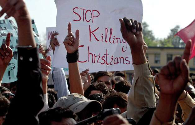 Pakistani Christians raise their hands during a demonstration demanding that the government rebuild their homes after they were burned down following an alleged blasphemy incident, in Islamabad, Pakistan, Sunday, March 10, 2013. The incident in Lahore began on Friday, March 8, 2013 after a Muslim accused a Christian man of blasphemy, an offence that in Pakistan is punished by life in prison or death. (AP Photo/Anjum Naveed) Photo: Anjum Naveed
