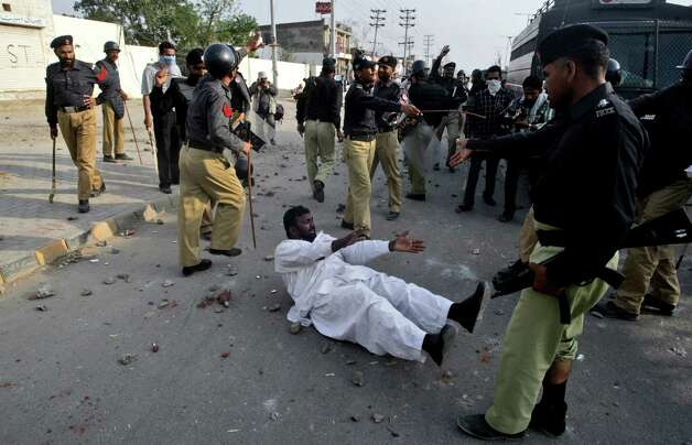 A Pakistani protestor is seen on the ground after being detained by police, during clashes in Lahore, Pakistan, Sunday, March 10, 2013. Hundreds of Christians protesting the burning of their homes by a Muslim mob over alleged blasphemous remarks made against the Islam's Prophet Muhammad clashed with police on Sunday in eastern and southern Pakistan. (AP Photo/K.M. Chaudary) Photo: K.M. Chaudary