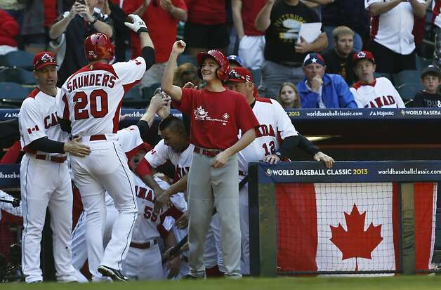 Canada's Michael Saunders (20) celebrates his home run against the United States with coach Denis Boucher, left, and a batboy in the second inning of a World Baseball Classic baseball game on Sunday, March 10, 2013, in Phoenix. (AP Photo/Ross D. Franklin) Photo: Ross D. Franklin, Associated Press