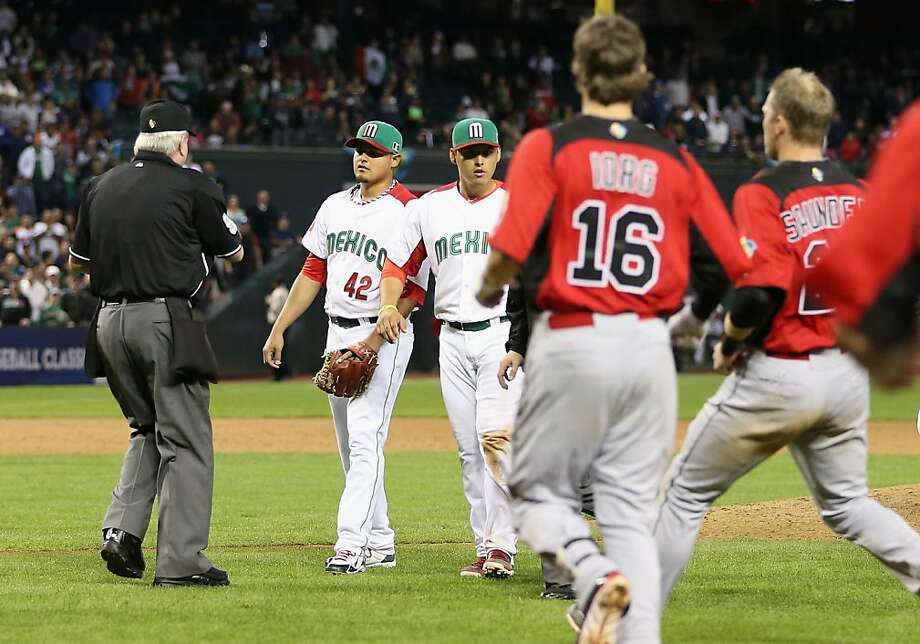 Home plate umpire Brian Gorman ejects Mexico pitcher Arnold Leon (42), an A's farmhand, after he hit Rene Tosoni (not pictured) during the ninth inning. Photo: Christian Petersen, Getty Images