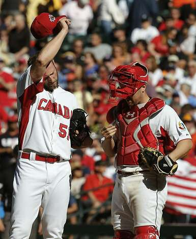 Canada's Jim Henderson, left, wipes his head as he pauses with teammate Chris Robinson after giving up a run to the United States in the eighth inning of a World Baseball Classic baseball game on Sunday, March 10, 2013, in Phoenix.  The United States defeated Canada 9-4. (AP Photo/Ross D. Franklin) Photo: Ross D. Franklin, Associated Press