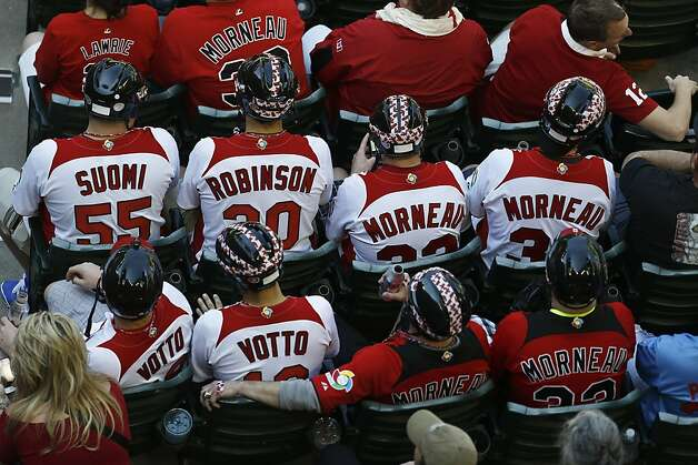 Canada baseball fans wear hockey helmets as they watch Canada play the United States in the fourth inning during a World Baseball Classic baseball game on Sunday, March 10, 2013, in Phoenix. (AP Photo/Ross D. Franklin) Photo: Ross D. Franklin, Associated Press