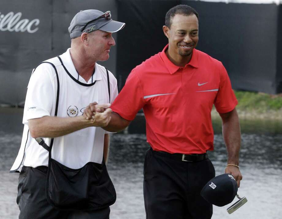 Tiger Woods (right) and caddie Joe Lacava congratulate each other after winning the Cadillac Championship. Woods now has five victories in the past year, the most of anyone in the world. Photo: Wilfredo Lee / Associated Press