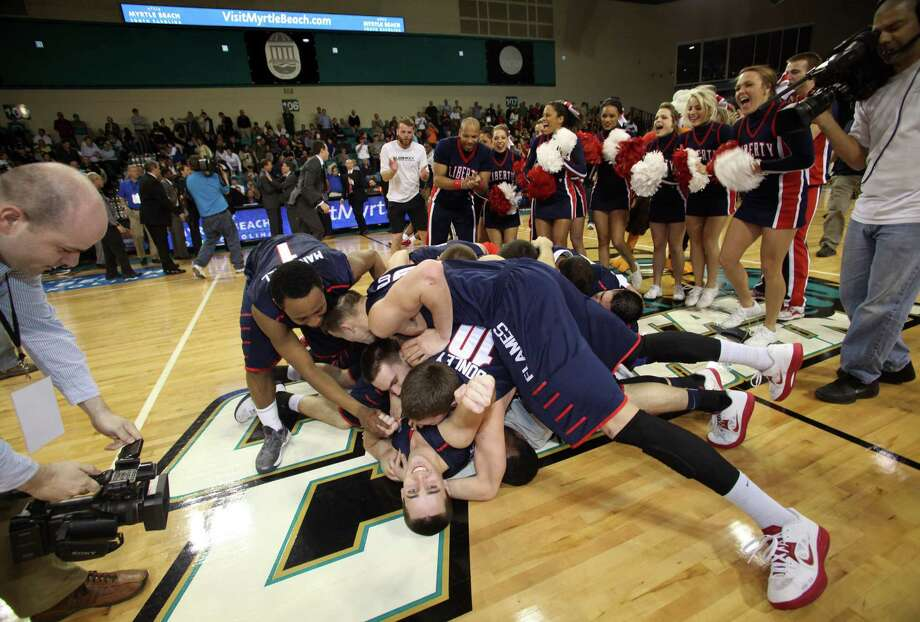 Liberty players exult at midcourt after beating Charleston Southern 87-76 to win the Big South tournament. The Flames (15-20) are the second 20-loss team to earn an NCAA tournament bid. Photo: Willis Glassgow / Associated Press