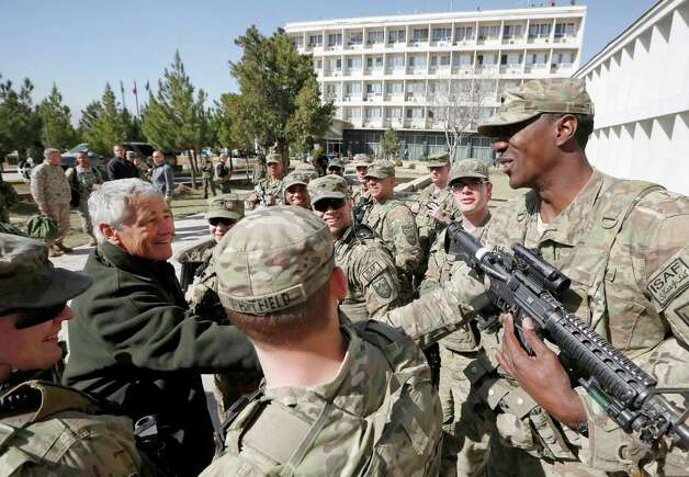 U.S. Secretary of Defense Chuck Hagel, left, is greeted by members of the U.S. Army and Marines during his visit to the Kabul Military Training Center in Kabul, Afghanistan, Sunday, March 10, 2013. Hagel is on his first trip to Afghanistan as defense secretary. (AP Photo/Jason Reed, Pool) Photo: Jason Reed