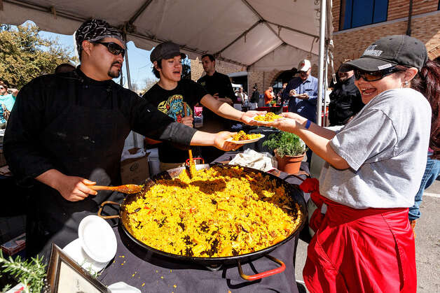Elia Jasso gets paella Sunday from J.C. Rodriguez (center) and Chef Jeff Balfour. The Corona Paella Challenge, hosted by La Gloria Chef Johnny Hernandez, benefits the educational foundation of the San Antonio Hispanic Chamber of Commerce and the Culinary Institute of America San Antonio. Photo: Marvin Pfeiffer / San Antonio Express-News