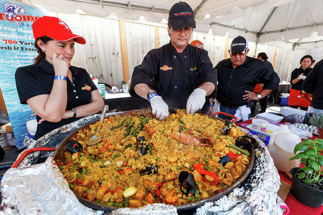 Chef Eric Paz (center) puts the finishing touches on his paella as Kathy Paz (left) and Luis Borrero look on during the 4th Annual Corona Paella Challenge, hosted by La Gloria chef, Johnny Hernandez, on the grounds of the Pearl Brewery on Sunday, March 10, 2013.  Twenty-five of the top chefs in this country and throughout Latin America competed in the event as well as five area high schools. Photo: Marvin Pfeiffer / San Antonio Express-News / Express-News 2013