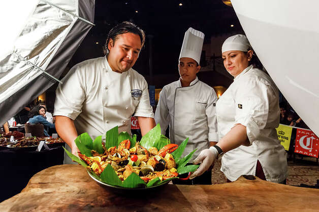 Chef Johnny Hernandez (left) takes the paella dish prepared by Chef Jhojan Preigo Zarate from Veracruz, Mexico (center) and Paula Torroella to the judges table during the 4th Annual Corona Paella Challenge, hosted by Hernandez, on the grounds of the Pearl Brewery on Sunday, March 10, 2013.  Twenty-five of the top chefs in this country and throughout Latin America competed in the event as well as five area high schools. Photo: Marvin Pfeiffer / San Antonio Express-News / Express-News 2013