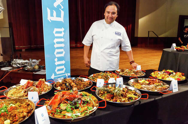 La Gloria chef, Johnny Hernandez, host of the 4th Annual Corona Paella Challenge on the grounds of the Pearl Brewery, stands with entries awaiting judging in the contemporary paella division on Sunday, March 10, 2013.  Twenty-five of the top chefs in this country and throughout Latin America competed in the event as well as five area high schools. Photo: Marvin Pfeiffer / San Antonio Express-News / Express-News 2013