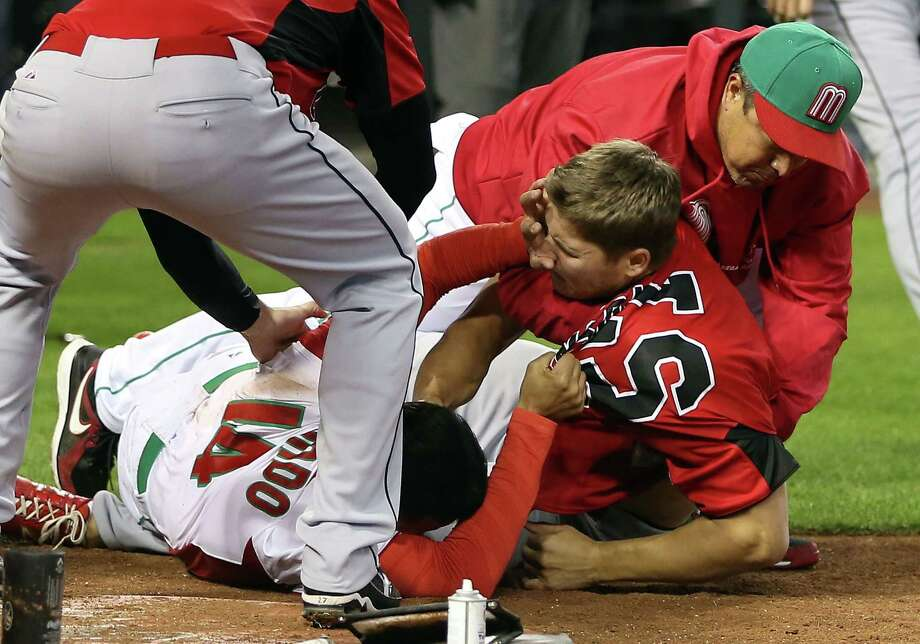 Eduardo Arredondo, left, of Mexico and Jay Johnson of Canada mix it up during Saturday's brawl in the Canadians' 10-3 win in the World Baseball Classic. Photo: Christian Petersen, Staff / 2013 Getty Images