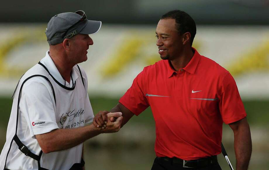 Caddie Joe LaCava congratulates Tiger Woods on his second win of the season and No. 76 of his career, six shy of Sam Snead's all-time reocrd. Photo: Warren Little, Staff / 2013 Getty Images