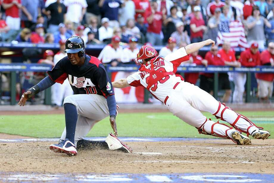 Adam Jones slides past Canadian catcher Chris Robinson to score during a four-run, eighth-inning rally that put the U.S. ahead to stay. Photo: Christian Petersen, Staff / 2013 Getty Images