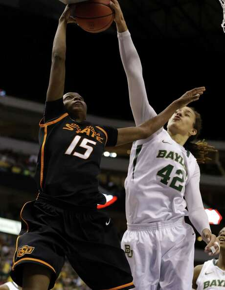 Baylor center Brittney Griner blocks the shot of Oklahoma State's Toni Young in the second half of the Lady Bears' 77-69 Big 12 tournament victory Sunday. Photo: Tony Gutierrez / Associated Press