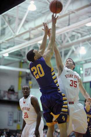 Gary Johnson of UAlbany, left, puts up a shot over Scott King of Stony Brook during their game at the SEFCU Arena on Sunday, March 10, 2013 in Albany, NY.  (Paul Buckowski / Times Union) Photo: Paul Buckowski