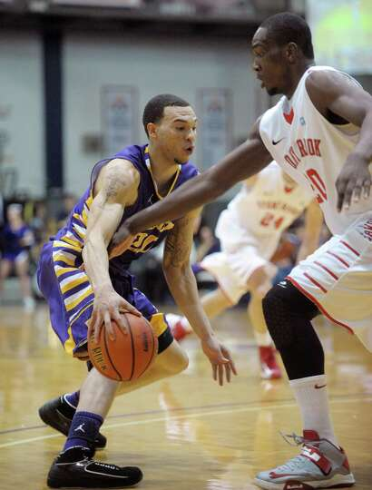 Gary Johnson of UAlbany, left,  tries to get around a Stony Brook defender during their game at the