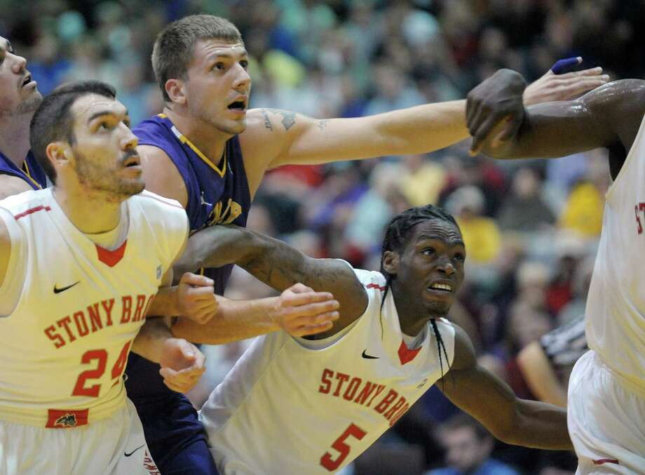 Blake Metcalf of UAlbany, center, tries to get through Tommy Brenton, left, and Dave Coley, rigiht, of Stony Brook during their game at the SEFCU Arena on Sunday, March 10, 2013 in Albany, NY.  (Paul Buckowski / Times Union) Photo: Paul Buckowski